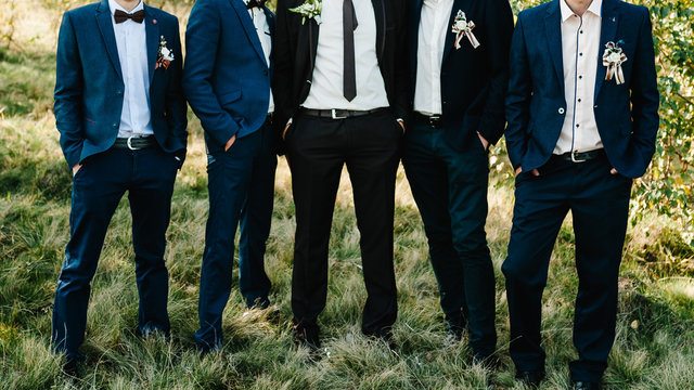 Wedding portrait groomsmen and groom. Young friends groomsman posing for camera. Cheerful friends outdoors. Wedding day.