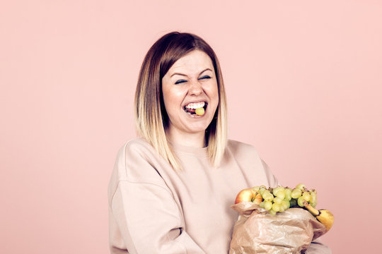 attractive positive woman with holding a paper bag full with  fruits - healthy eating and lifestyles concept