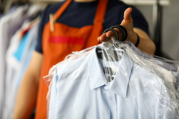 Clothes dry cleaning service worker returning shirts to customer