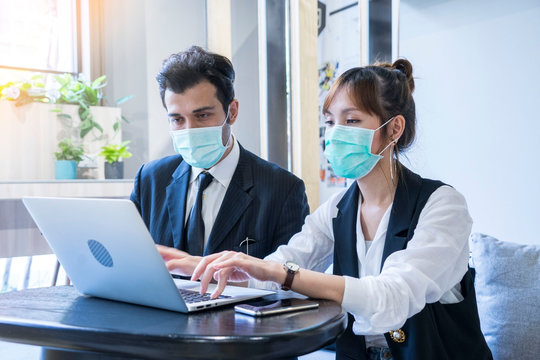 sian female and Businessman workers meeting together with laptop and wear protective masks prevent PM 2.5 and corona viruus or covic19 at co working space .Health and teamwork concept