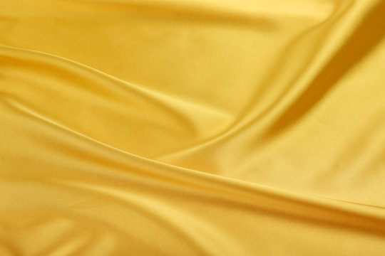 yellow satin fabric with creases. golden fabric texture
