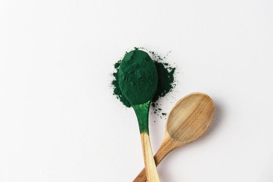 Wooden spoons with spirulina powder, superfood on a white background, green algae powder, smoothie, drink, healthy eating