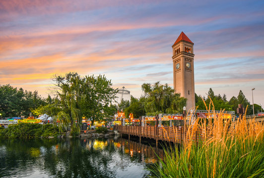Festival goers enjoy a colorful sunset at the annual Pig out in the Park at Riverfront Park along the Spokane River in Spokane, Washington