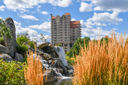A tourist resort hotel in Coeur d'Alene Idaho rises above the memorial waterfall and pond in McEuen Park on a summer day in the Inland Northwest