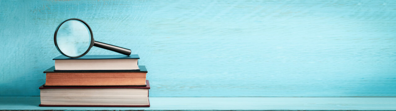 A magnifying glass on a stack of books on a blue wooden bookshelf with copy space web banner