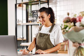 Young shop owner using a laptop. Florist woman standing at counter. - fototapety na wymiar