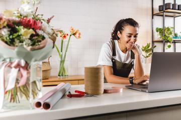 Obraz Smiling flower shop owner using laptop computer. Female florist working on laptop at counter. - fototapety do salonu