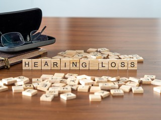 hearing loss concept represented by wooden letter tiles on a wooden table with glasses and a book