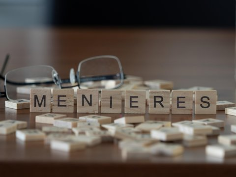 menieres concept represented by wooden letter tiles on a wooden table with glasses and a book