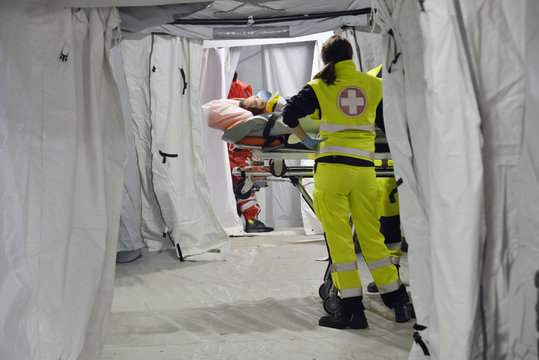 Doctor with protection mask checking patient with Corona Virus on the stretcher inside a hospital field tent for the first AID. Camp room for people infected with an epidemic.