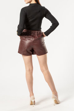 short brown shorts with a leather belt close-up , women's legs in black high-heeled shoes on a white background, a girl in a short leather skirt