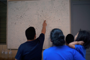 Honduran migrants, sent back to Guatemala from the United States under an Asylum Cooperative Agreement (ACA), look at a map at Casa del Migrante shelter in Guatemala City