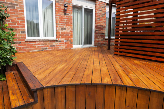 Backyard wooden deck floor boards with fresh brown stain