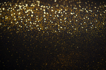 Beautiful Christmas light background. Abstract glitter bokeh and scattered sparkles in gold, on black Wall mural
