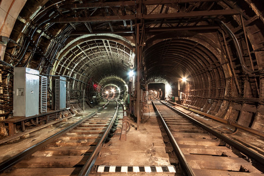 Two railway lines are laid next to each other. The railway line turns to the left, the railway line runs straight. A brightly illuminated tunnel with reinforced concrete walls. Electric cables.