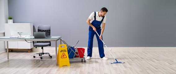 Worker Mopping Floor With Wet Floor Caution Sign