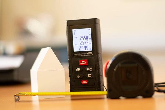 length measuring instrument, laser meter, meter, ruler, white model of house