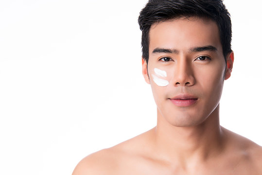Portrait of young handsome man applying cream lotion on face, isolated on white background