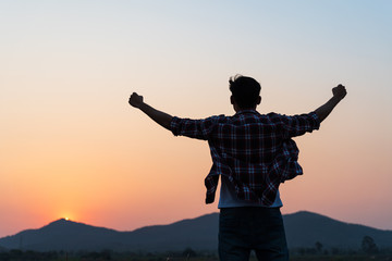 Man with fist in the air during sunset sunrise mountain in background. Stand strong. Feeling motivated, freedom, strength and courage concept.