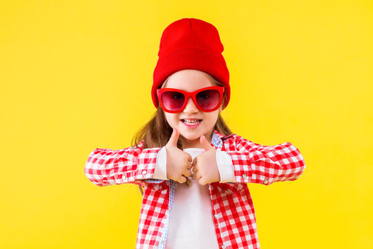 Cheerful stylish little girl dressed in pink checkered shirt, red cap, sunglasses, jeans on yellow background. Smiling cute child is showing with hands sign of like, thumbs up. Emotional portrait.