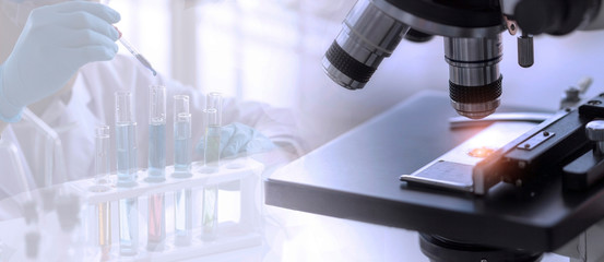 Laboratory concept; close up of microscope with a blurred picture of the scientist is researching in laboratory