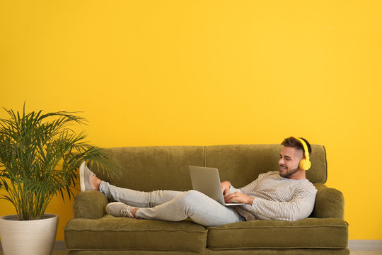 Young man with laptop and headphones resting on sofa at home