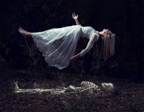 Levitation image of a woman rising from a skeleton on dead leaves