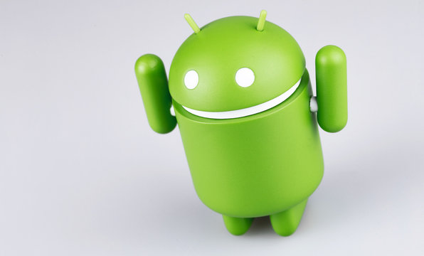 Google Android figure with raised hands on grey background. Google Android is the operating system for smartphones, tablet computers, e-books and other devices. Moscow, Russia - March 19, 2019