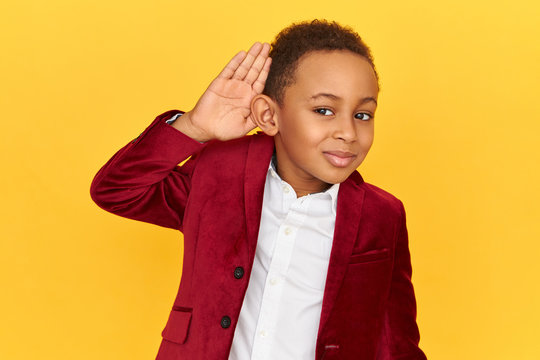 Studio shot of adorable snoopy dark skinned little boy having curious look, holding palm at his ear to hear more clearly while overhearing private conversation. Body language, signs and gestures