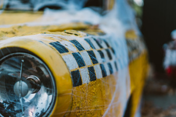 Old retro yellow taxi decorated with cobwebs
