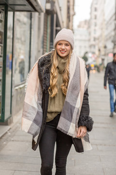 Beautiful young woman in winter autumn outfit walking in the city street