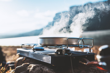 Spoed Foto op Canvas Kamperen camping cooking in nature outdoor, prepare breakfast picnic; cooker food metal gas stove on stone; tourism recreation outside; campsite lifestyle, hot food hiking trip
