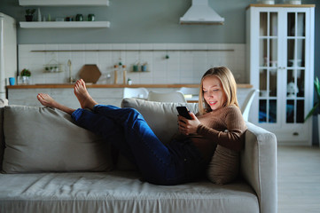 Woman use of smartphone in the evening at home while laying on sofa
