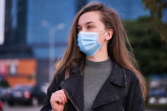 Woman wearing medical protective mask outdoors. Health protection during flu virus outbreak, coronavirus epidemic infectious diseases and air pollution in the city