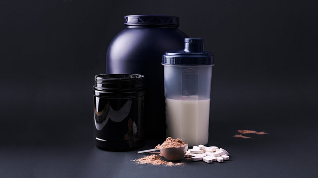 Sports nutrition supplements on a black background. Fitness, bodybuilding, healthy lifestyle concept. Whey protein powder in measuring scoop. Copy space