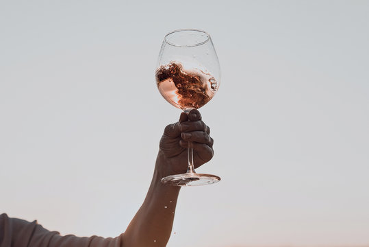 Glass of wine with splashes in woman's hand against the sunset sky.
