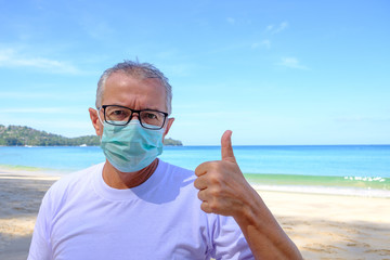 Mature man in white t-shirt and medical mask on his face showing thumbs up on beach background