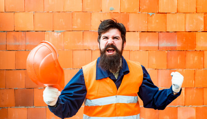 Success. Successful builder shows a gesture of success. Happy owner of the construction business. Building permit. Happy bearded builder.