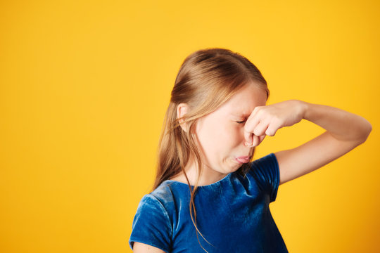 Little Redhead Girl Covering Nose For Bad Smell