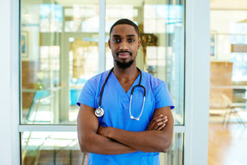 Portrait of a serious young male doctor or nurse wearing blue scrubs uniform and stethoscope, with arms crossed in hospital Wall mural