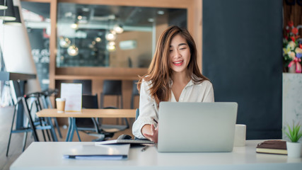 Charming asian businesswoman sitting working on laptop in office.