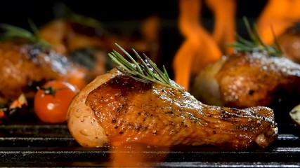 Wall Mural - Close up grill roast bbq chicken leg with addition herbs and spices on the flaming grill .