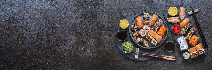 Photo sur Plexiglas Sushi bar sushi rolls with rice and fish, soy sauce on a dark stone background