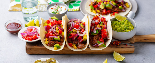 Taco with meat and vegetables on cutting board. Grey background. Close up. Wall mural