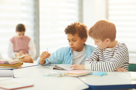 Horizontal portrait of two middle school male students sitting at desk in modrn classroom completing task together, copy space