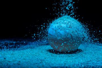 Salt falls on the blue bath ball. Bath ball with essential oils. The ball looks like a planet.
