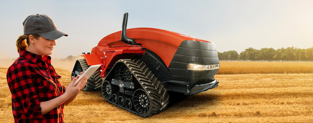 Wall Mural - Woman farmer with digital tablet controls autonomous tractor on a smart farm