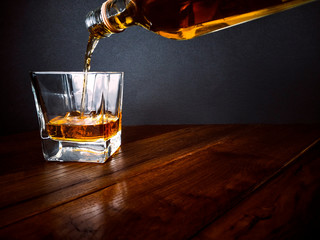 Pouring whisky into glass on wooden table - serve whiskey