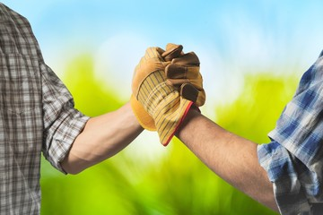 Two male farmers in gloves shaking hands
