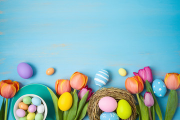 Easter holiday background with easter eggs and tulip flowers on wooden table.
